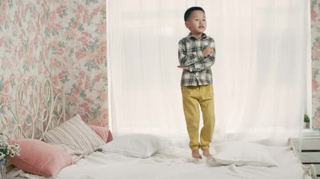 азиаты : the little boy of Asian appearance, having fun on the bed in the room, laughing and jumping, slow motion Стоковые видеозаписи
