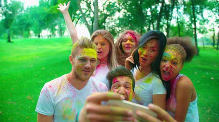 mob : cheerful company of young friends having fun in the Park with the colors of Holi make a selfie