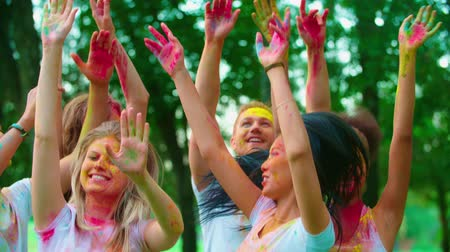 félrebeszél : group of young friends in the Park with the colors of Holi, dancing and having fun, close-up
