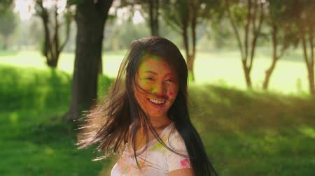 gençlik kültürü : closeup Asian beautiful girl having fun in the Park with the colors of Holi,slow motion