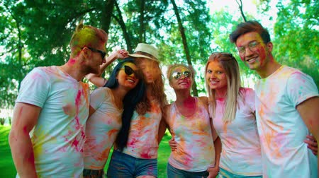 fan fest : cheerful company of young of different nationality friends having fun in the Park with the colors of Holi