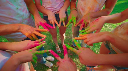 mob : cheerful company of young friends having fun in the Park with the colors of Holi Stock Footage