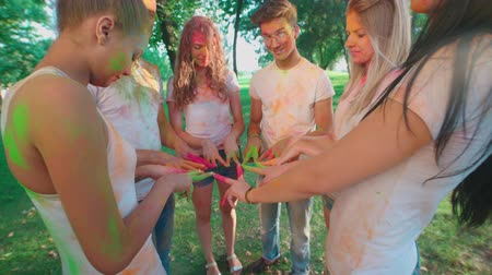 camera panning : cheerful company of young friends having fun in the Park with the colors of Holi Stock Footage