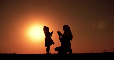 parte : silhouette of mother and little daughter playing at sunset, slow motion