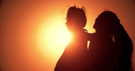 parte : silhouette of mother and little daughter playing at sunset, slow motion, close-up Stock Footage