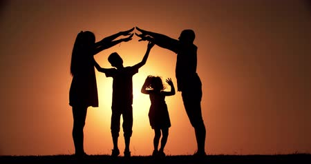 investimento : 4K, home concept, family silhouette father, mother, two children, dream of buying a house, playing in the background of the sunset, slow motion Vídeos