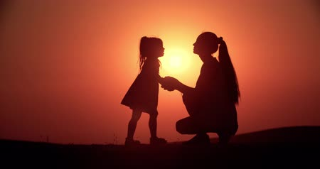 parte : silhouette of mother and little daughter having fun playing at sunset, slow motion