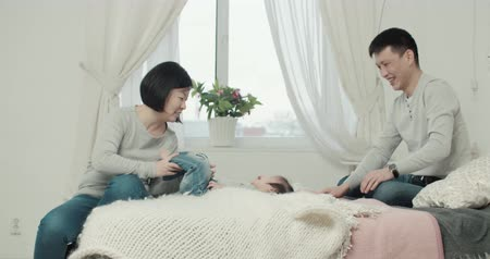 утешитель : slow motion, young happy Asian couple with a little girl in the bedroom,happy moments in the family