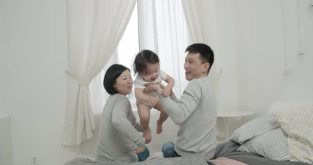 утешитель : slow motion, little cheerful Asian girl playing with her parents ,moments of happiness in the family