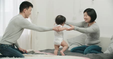 anlamı : slow motion, young happy Asian couple with a baby in the bedroom,happy moments in the family