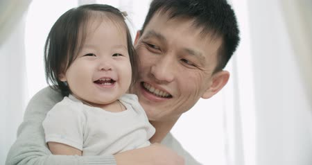 anlamı : slow motion, little cheerful Asian girl playing with her parents ,moments of happiness in the family