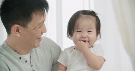 significado : slow motion, little cheerful Asian girl playing with her parents ,moments of happiness in the family