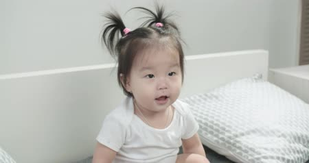 pelenka : slow motion, close-up, babe Asian 1 year,having fun on the bed in the room , emotionally expresses joy Stock mozgókép