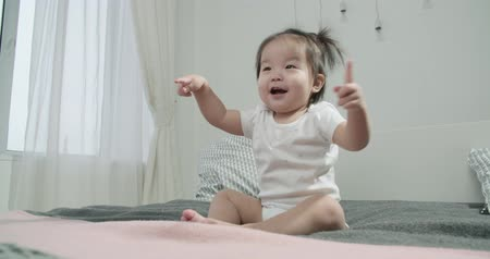 pelenka : slow motion, little Asian girl 1 year baby ,having fun on the bed in the room , emotionally expresses joy
