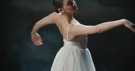 poddasze : 4K video footage closeup of a beautiful female ballet dancer on black background, slow motion