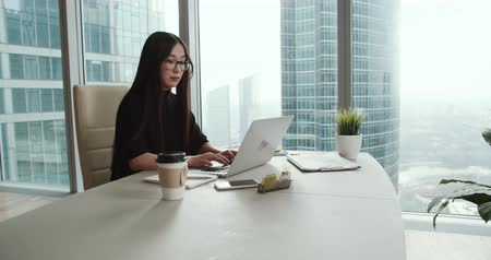 bund : young successful Asian business girl in a modern office skyscraper, working using laptop