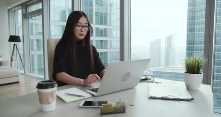 tezgâhtar : closeup Asian girl in a modern office, business correspondence using a laptop Stok Video