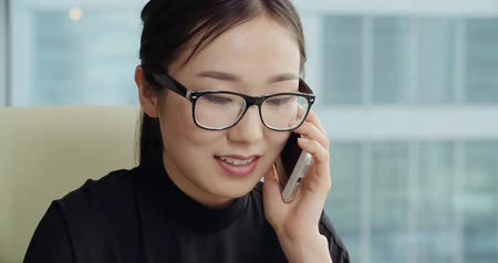 markalaşma : Asian girl with a smile talking on the phone in a modern office,Steadicam shot, close-up Stok Video