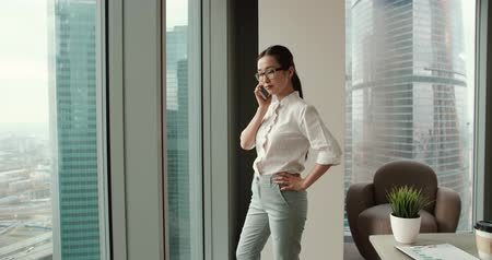 tezgâhtar : Asian girl busy talking on the phone walks in a modern office,the business situation around