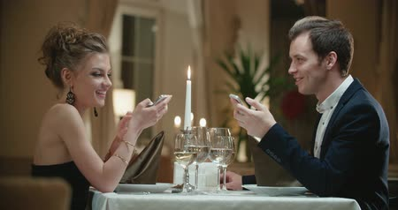 słoneczko : couple at the restaurant on the first date, the smartphone helps to find a way to communicate without shyness Wideo