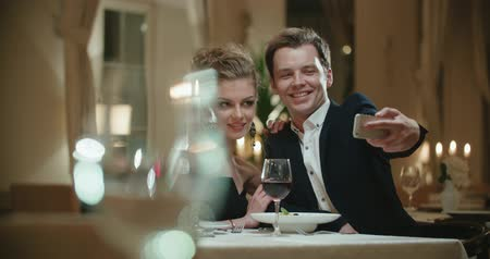 seçkinler : couple at the restaurant on the first date, take a selfie using a smartphone Stok Video