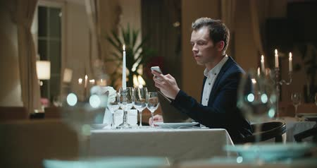 annoyance : a lonely young man in the restaurant with a smartphone waiting for a woman on a date