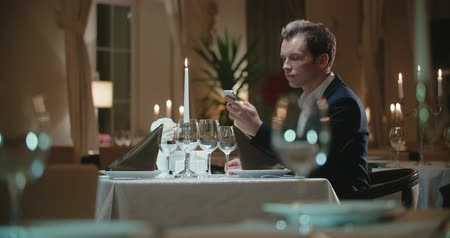impatience : a lonely young man in an expensive restaurant uses a smartphone waiting for a woman on a date,Dolly shot