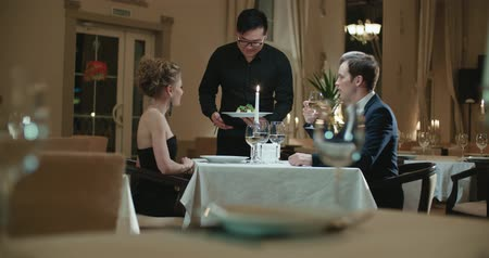официант : the young Asian waiter serving couple in restaurant for dinner