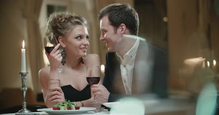 enjoyable : young couple with a glass of wine in the restaurant , flirting on a date Stock Footage