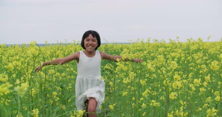 arejado : little Asian girl 8-9 years of laughs, smiles and runs across the field of yellow flowers, slow motion