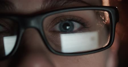 maniac : woman with glasses eyes looking at the monitor, surfing the Internet, extreme close-up, dark room