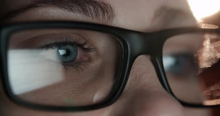 zombi : woman in glasses and blue eyes looking at the monitor, surfing the Internet, extreme close-up with reflection Stok Video