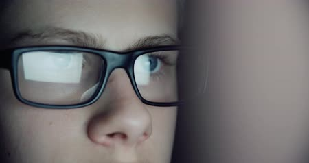 szemgolyó : 12 years teen puberty eye glasses looking at the monitor in a dark room,surfing the Internet, close-up