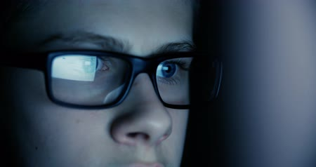 gyerekes : teen boy eyes in the glasses looking at the monitor in a dark room,surfing the Internet, close-up