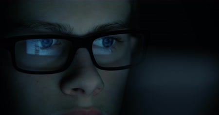 globo ocular : teen boy eyes in the glasses looking at the monitor in a dark room,surfing the Internet, close-up