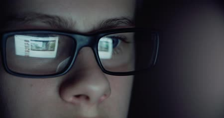 globo ocular : 12 years teen puberty eye glasses looking at the monitor in a dark room,surfing the Internet, close-up