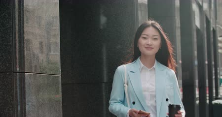 goes : beautiful young business Asian woman in a good mood in the morning, goes to work with smartphone and coffee to go, slow motion Stock Footage