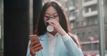 goes : beautiful young business Asian girl goes to work with smartphone and coffee to go, slow motion