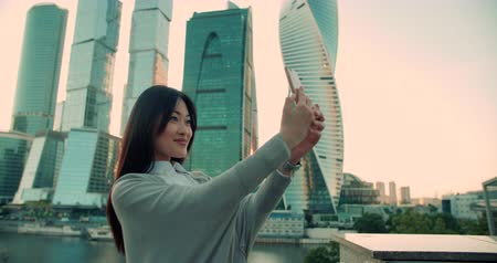 skyscraper : beautiful girl Asian model is making a selfie on the background of skyscrapers using a smartphone