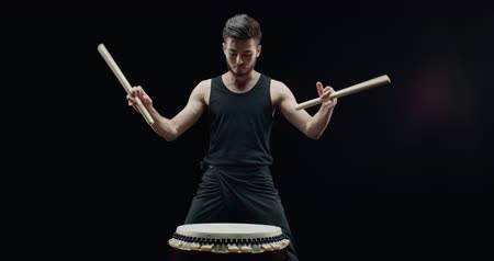 gagaku : the beginning of a performance of Taiko , Asian male drummer in black clothes suitable to the drums and starts to beat the rhythm
