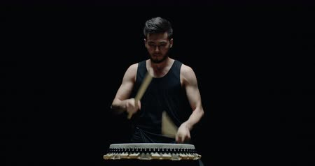 барабанщик : performance of Taiko , Asian male drummer in black clothes is very expressive beats the rhythm on a Japanese drum,black background