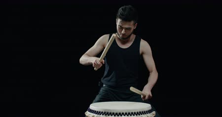 vurmalı : performance of Taiko , Asian male drummer in black clothes, beats a rhythm on a Japanese drum, Steadicam shot, black background Stok Video