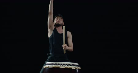 musical intrument : performance of Taiko , a detail shot Asian male drummer in black clothes, beats a rhythm with the jumping on the Japanese drum ,black background Stock Footage