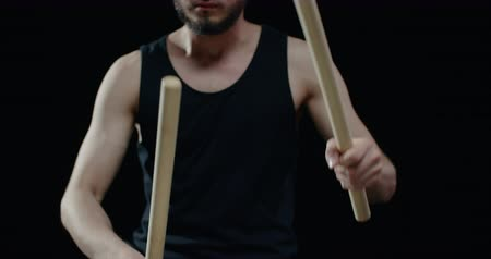 gagaku : performance of Taiko , close-up Asian male drummer in black clothes, beats a rhythm on a Japanese drum,black background