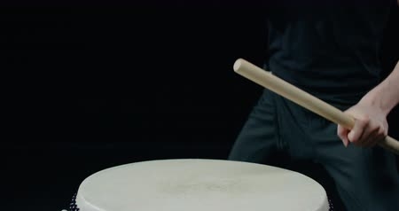 barulhento : performance of Taiko , a detail shot Asian male drummer in black clothes, beats a rhythm on a Japanese drum,black background