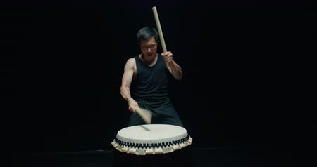gagaku : performance of Taiko , Asian male drummer in black clothes is very expressive beats the rhythm on a Japanese drum,black background