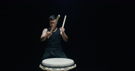gagaku : performance of Taiko , Asian male drummer in black clothes, beats a rhythm on a Japanese drum, Steadicam shot, black background Stock Footage