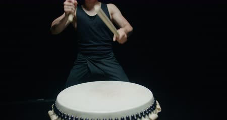 vurmalı : performance of Taiko , Asian male drummer in black clothes is very expressive beats the rhythm on a Japanese drum,black background