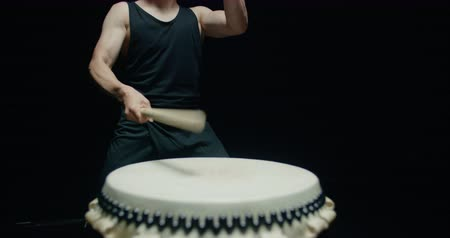 hachimaki : performance of Taiko , close-up Asian male drummer in black clothes, beats a rhythm on a Japanese drum,black background