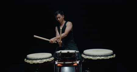musical intrument : performance of Taiko , Asian male drummer in black clothes, beats a rhythm on three Japanese drums Stock Footage